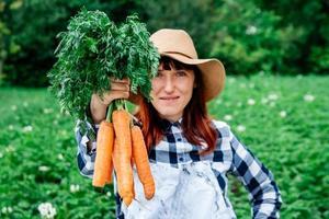 femme tenant des carottes photo