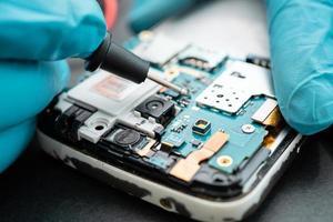 technicien réparant l'intérieur du téléphone portable en fer à souder. photo