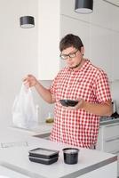 homme tenant un sac en plastique jetable avec livraison de nourriture à la cuisine photo