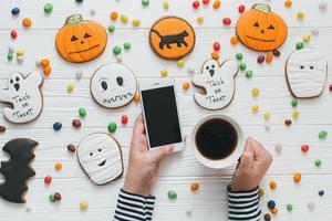une préparation pour Halloween. femme tenant un café et un smartphone. photo