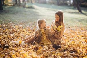mère et sa fille assises et s'amusant dans le parc en automne. photo