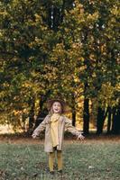 une petite fille vêtue d'une robe jaune et d'un manteau beige se promène dans un parc d'automne photo