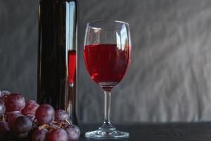 vin rouge et bouteille de vin avec des raisins sur fond noir photo