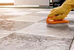 à l'aide d'une brosse à plancher en plastique pour frotter le sol carrelé. photo