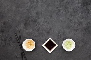 vue aérienne sauce soja wasabi au gingembre mariné avec tableau noir de baguettes. résolution et haute qualité belle photo