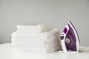 vue de face pile de serviettes avec fer à repasser. résolution et haute qualité belle photo