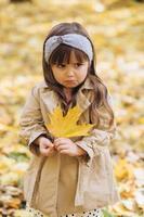 Petite fille offensée tenant une feuille d'érable jaune dans le parc d'automne photo