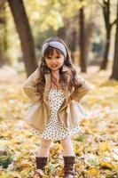 belle petite fille dans un manteau beige montre en colère dans le parc en automne photo
