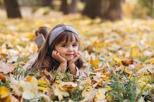 belle petite fille se trouve parmi les feuilles jaunes dans le parc d'automne photo