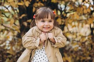 petite fille dans un manteau beige montre des émotions dans le parc d'automne photo