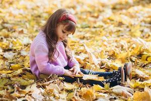 heureuse petite fille assise parmi les feuilles d'automne jaunes dans le parc photo