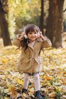 heureuse petite fille écoutant de la musique au casque dans le parc en automne photo