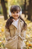 heureuse petite fille écoutant de la musique au casque dans le parc en automne. photo