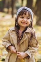 belle petite fille dans un manteau beige se promène dans le parc en automne photo
