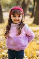 portrait d'une petite fille heureuse tenant une feuille dans le parc en automne photo