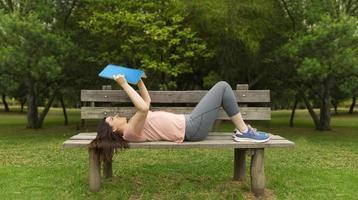 Jeune femme en vêtements de sport allongée sur le banc en bois en lisant un livre photo