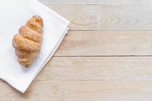 vue de dessus croissant frais sur tissu blanc avec table en bois photo