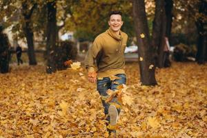 beau mec sourit et court en éparpillant des feuilles jaunes dans un parc en automne photo