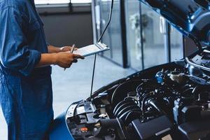 mécanicien automobile tenant le presse-papiers et vérifiant l'entretien photo