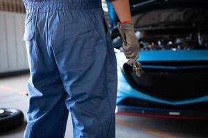 mécanicien automobile tenant une clé pour la fixation à la réclamation du client photo