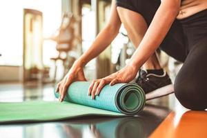 Close up of sporty woman pliage matelas de yoga photo