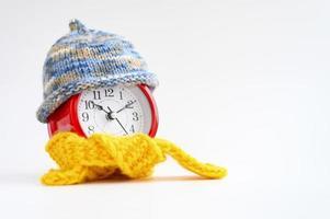 réveil rond rouge en tricot de laine bonnet bleu et écharpe jaune sur fond blanc. notion d'hiver. L'hiver. douillet et chaleureux. temps analogique 10 10. espace pour le texte. bannière photo