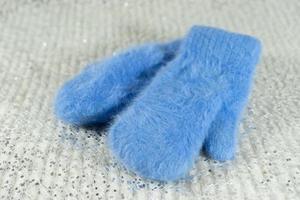 mitaines en laine bleue sur fond brillant photo
