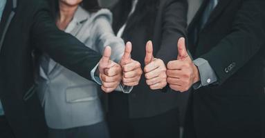 équipes de gens d'affaires donnant le pouce en l'air en se tenant debout au bureau photo