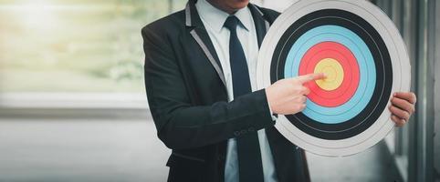 l'homme d'affaires pointe la cible de l'objectif sur le jeu de fléchettes photo