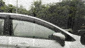 gouttes de pluie sur la fenêtre avec fond de voiture. photo