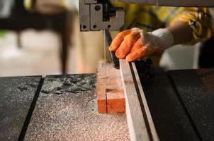 les femmes travaillent le bois coupé avec des outils électriques de scies à ruban photo