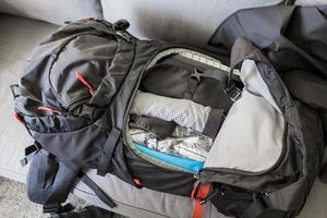 emballage sac à dos de voyage noir rouge emballé, vêtements et ustensiles de voyage. photo