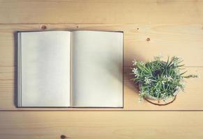 livre ouvert et verres sur table en bois avec vase à fleurs photo