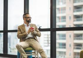 Jeune bel homme barbu d'affaires buvant une tasse de café photo