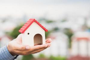 main tenant la maison de maquette. assurance pret immobilier photo