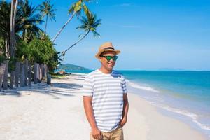heureux jeune homme sur la plage tropicale photo