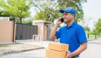 livreur bleu tenant une boîte en carton de colis et parlant au téléphone. photo