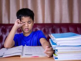 un garçon est fatigué de lire un livre sur une table en bois. photo