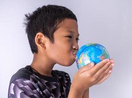 un garçon tend le globe et l'embrasse sur le globe. photo