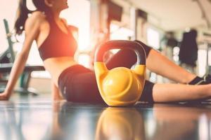 Close up kettlebells avec femme exercice d'entraînement en salle de sport photo