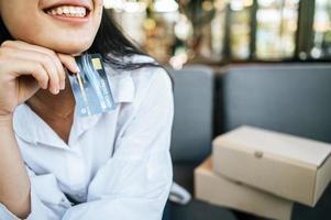 femme souriante tenant une carte de crédit photo