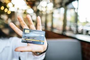 femme tenant une carte de crédit au restaurant photo