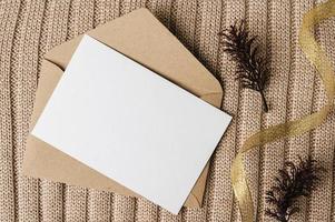 une carte vierge est placée sur une enveloppe et un pull photo