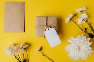 coffret cadeau avec étiquette vierge, enveloppe et fleurs est placé sur jaune photo