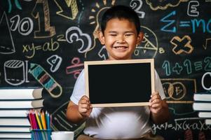 enfant assis et tenant un tableau noir dans la salle de classe photo