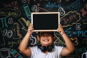 enfant tenant un tableau noir dans la salle de classe photo