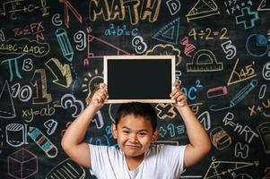 enfant debout et tenant un tableau noir dans la salle de classe photo