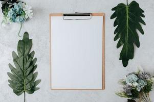 papier à lettres sur un morceau de bois avec des feuilles et des fleurs photo