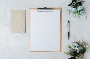 papier à en-tête, papier à en-tête et fleurs placés sur un fond blanc. photo