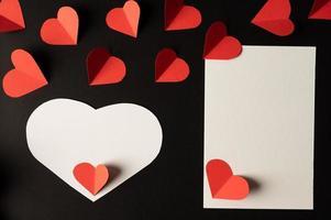 des coeurs blancs et des coeurs rouges en papier sont placés photo